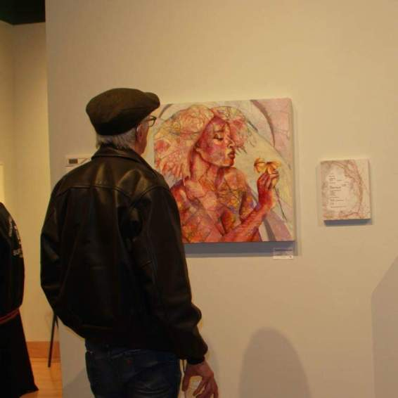 "Man looking at Nancy Smith's ""My Own Kind of Beautiful"" painting & V.C. McCabe's ""Night Garden"" poem"